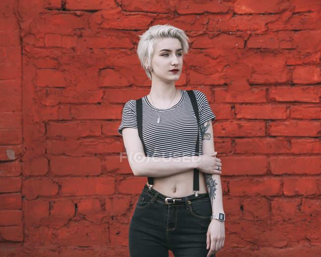 Fiduciosa giovane donna in piedi contro il muro di mattoni rossi e guardando altrove — Foto stock