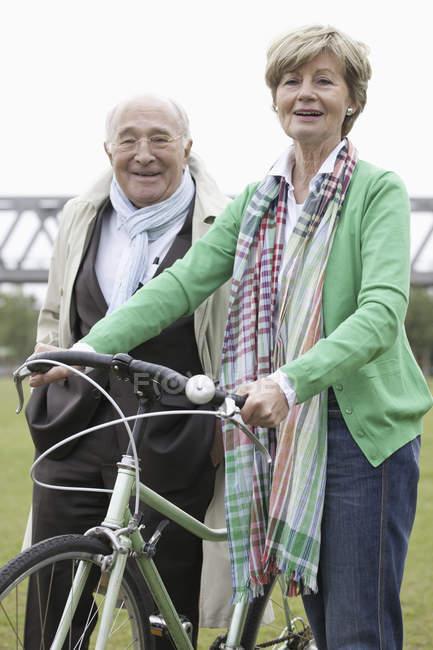 Счастливая пожилая пара, стоящая с велосипедом в парке — стоковое фото