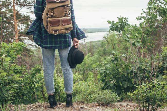 Baixa seção de fêmea mochileiro segurando chapéu enquanto em pé na floresta — Fotografia de Stock