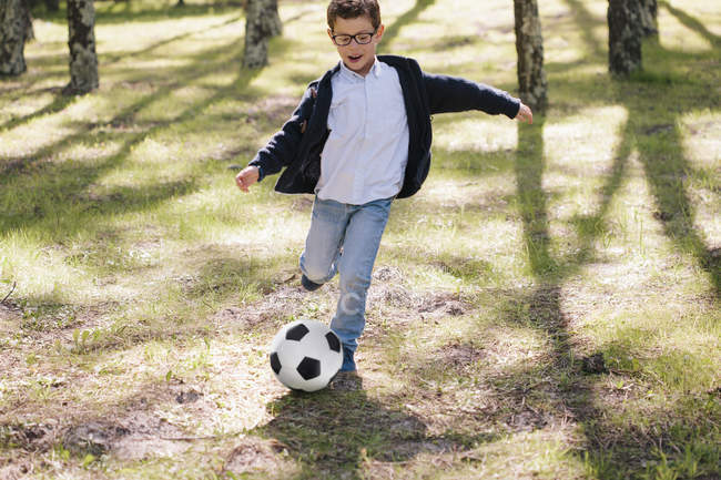 Happy boy playing soccer in forest — Stock Photo