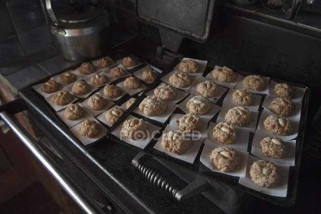 Close up view of cookies arranged on baking sheets in kitchen — Stock Photo
