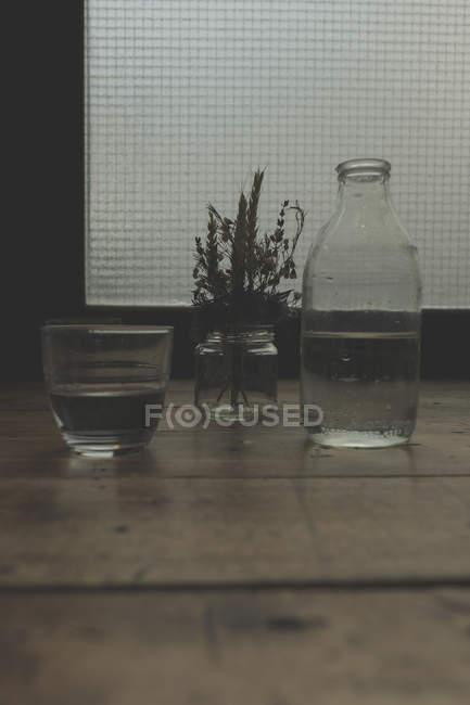 Закрыть вид на воду и завод в стеклянных контейнерах на столе — стоковое фото