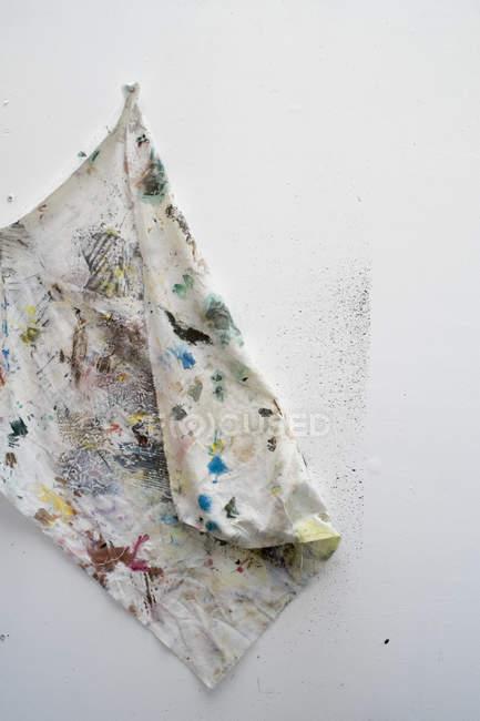Грязная салфетка с пятнами краски на белом фоне — стоковое фото