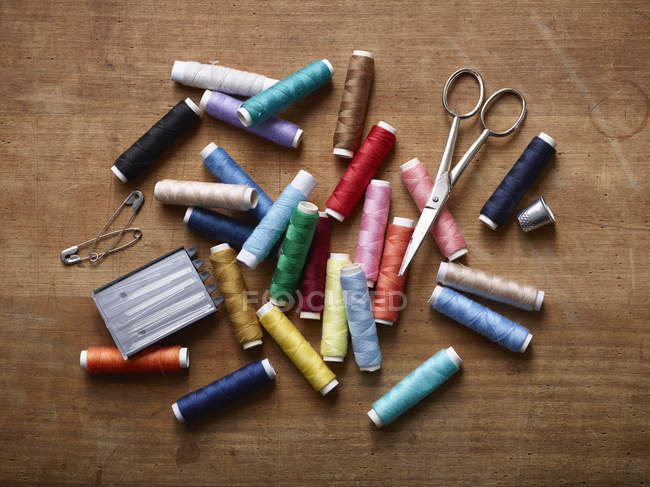 Various spools of colored thread in  pile with scissors, safety pins and sewing needles — Stock Photo