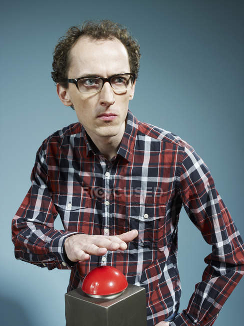 Nerdy guy with hand poised above red game show buzzer — Stock Photo