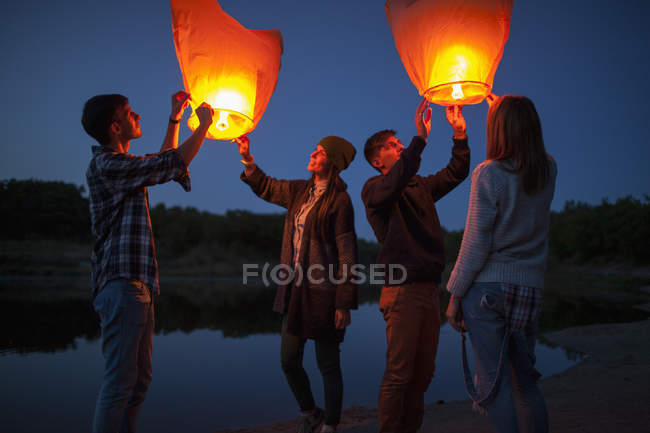 Male and female hikers releasing paper lanterns at lakeshore — Stock Photo