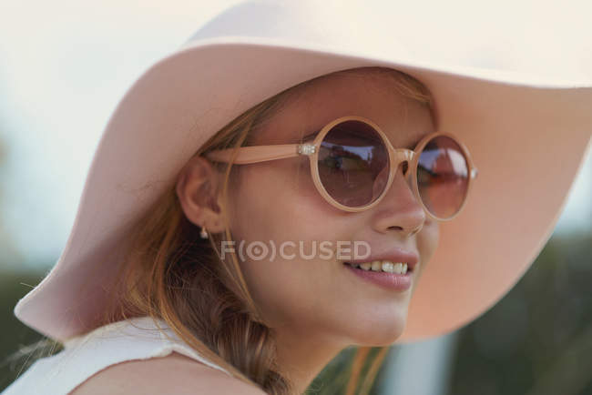 Portrait of young woman wearing sunglasses and hat in park — Stock Photo