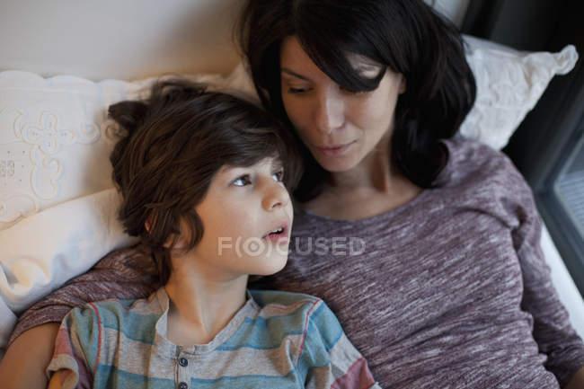 Мать и сын лежат и разговаривают в постели — стоковое фото