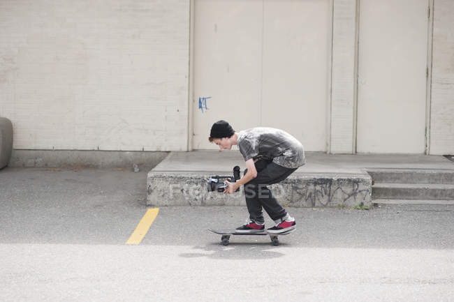 Full length side view of man video shooting while skateboarding outdoors — Stock Photo