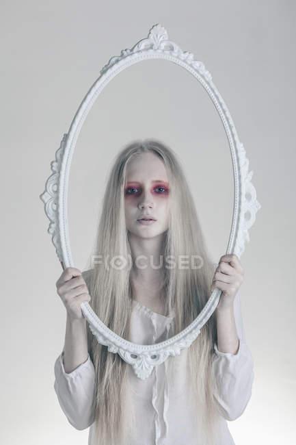 Ritratto di donna con gli occhi rossi spettrali che tengono cornice su sfondo bianco — Foto stock