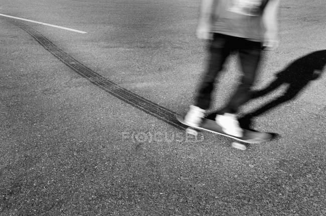 Crop skateboarder leaving tire tracks on asphalt — Stock Photo