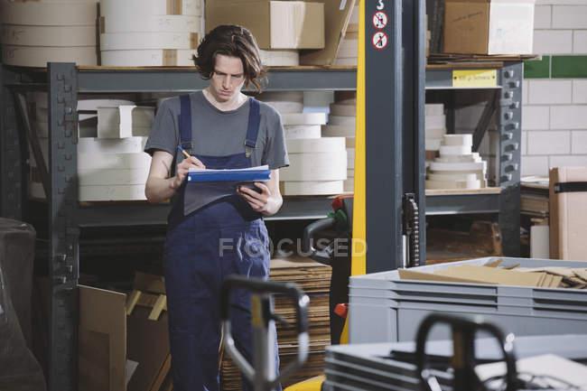 Молодой работник в комбинезоне пишет заметки на складе — стоковое фото