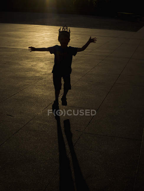 Silhouette of boy wearing crown dancing on pavement during sunset — Stock Photo