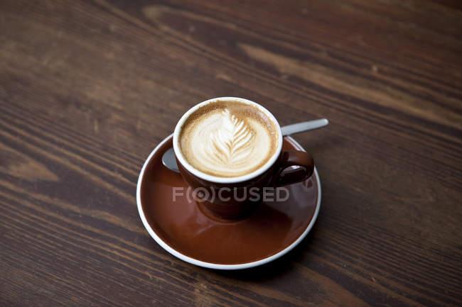 Латте з квітковим візерунком в молоко піна на стіл в кафе — стокове фото