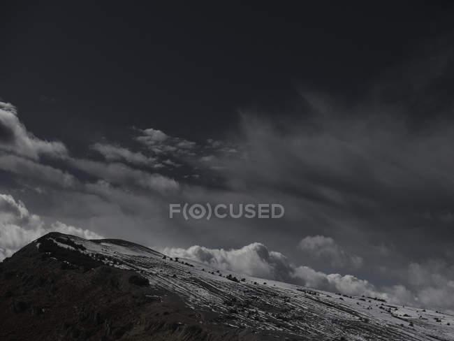 Drammatico paesaggio nuvoloso sopra il pendio innevato della montagna — Foto stock