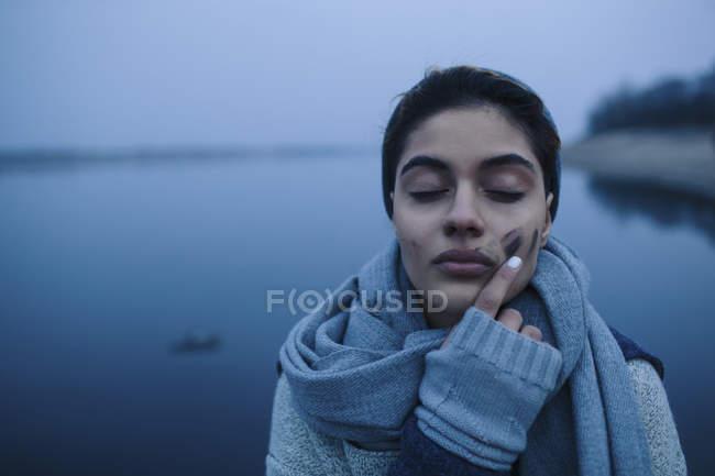 Девочка-подросток касается грязного лица на озере — стоковое фото