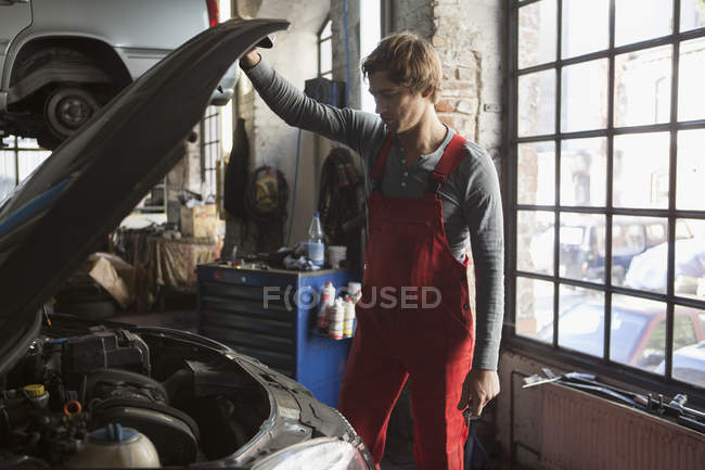 Meccanico esame motore auto in officina di riparazione — Foto stock