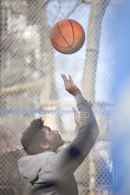 Young man playing basketball on public outdoor court — стоковое фото