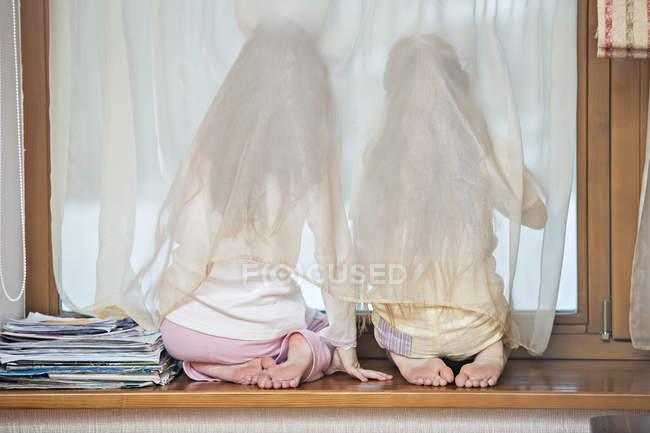 Vista traseira das irmãs sentada no peitoril da janela e olhando para fora da janela — Fotografia de Stock