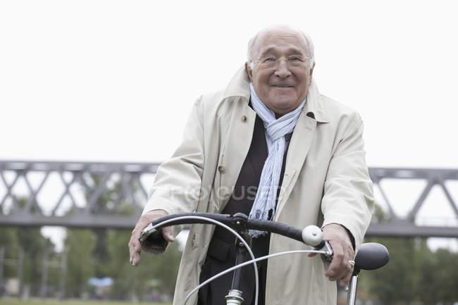 Hombre mayor ciclismo bicicleta en el parque - foto de stock