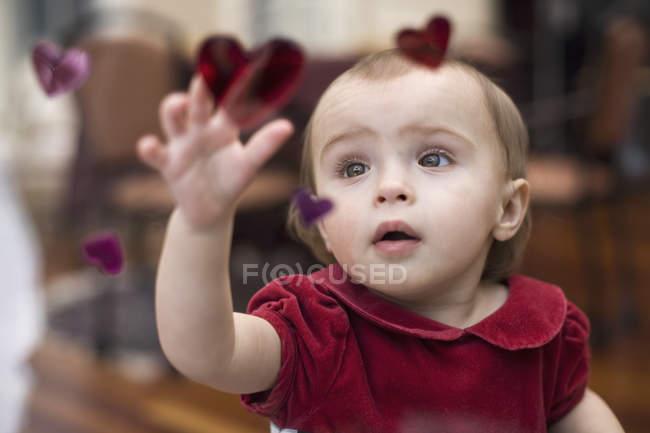 Дитина досягає вгору на дотик серце термоаппликації обрамлення вікон, переглядати через вікно — стокове фото