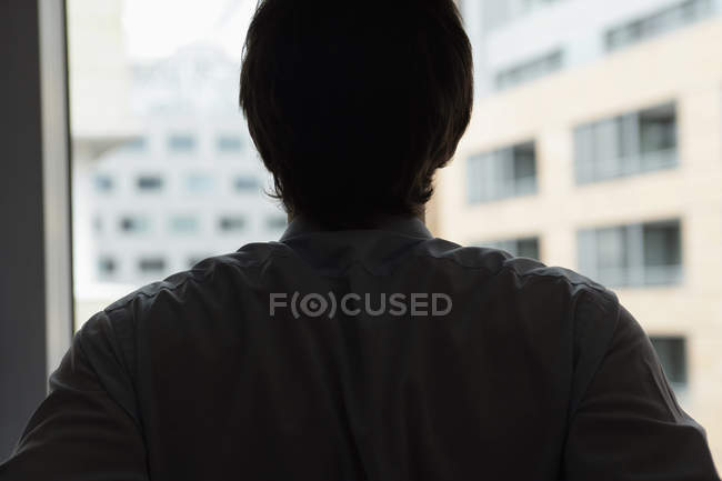 Silhouetted man standing at window — Stock Photo