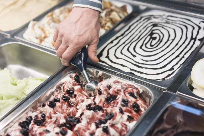 Crop hand scooping ice cream from container at store display — Stock Photo