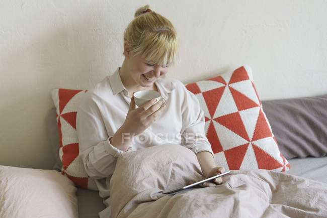 Smiling woman having coffee while using digital tablet on bed at home — Stock Photo