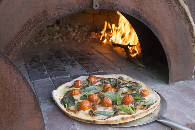Fresh pizza on peel in traditional oven — Stock Photo