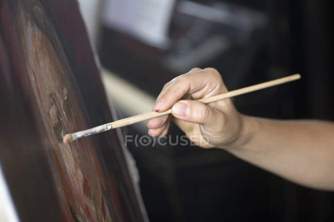 Crop female artist's hand painting with brush — Stock Photo