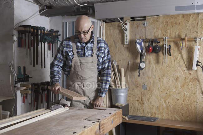 Зрелый человек, работающий в столярной мастерской — стоковое фото