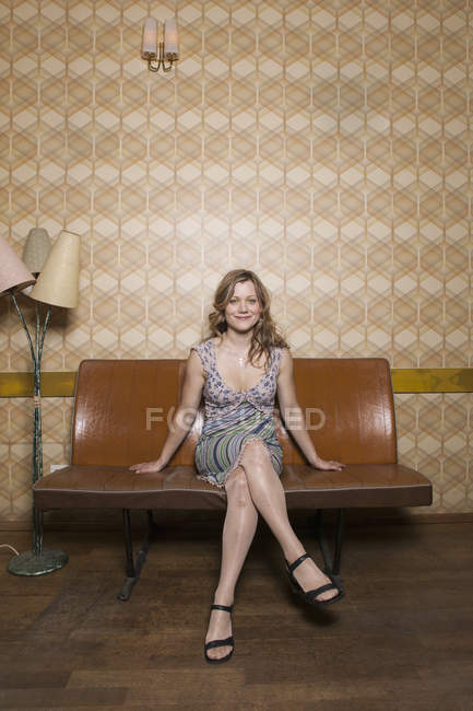 A smiling woman sitting in a retro styled room — Stock Photo