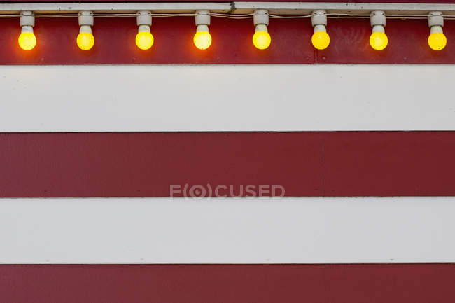 Reihe von beleuchteten Glühbirnen auf gestreifte Wand — Stockfoto