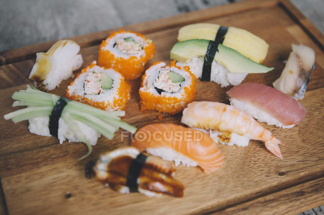 Low angle view of various sushi on cutting board — Stock Photo