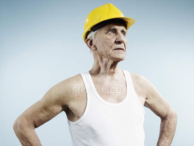 Senior-Mann mit Hut und Tank-Top auf blauem Hintergrund — Stockfoto