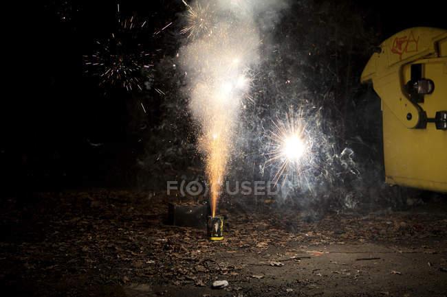 Faíscas e fumaça saindo do fogo de artifício explodindo na calçada — Fotografia de Stock