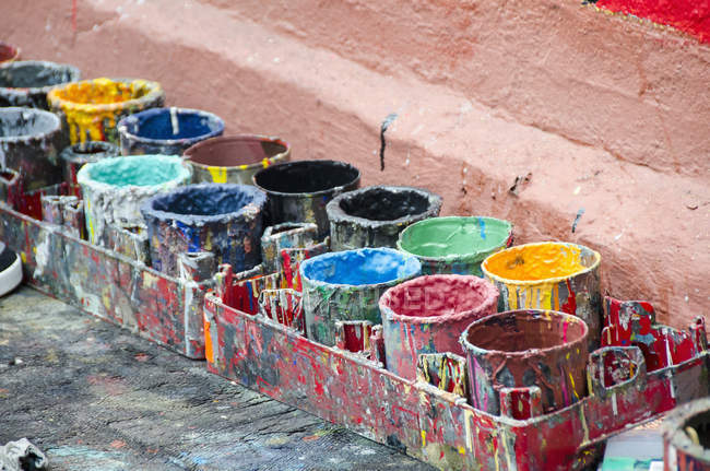 High angle view of colorful paint cans by wall — Stock Photo