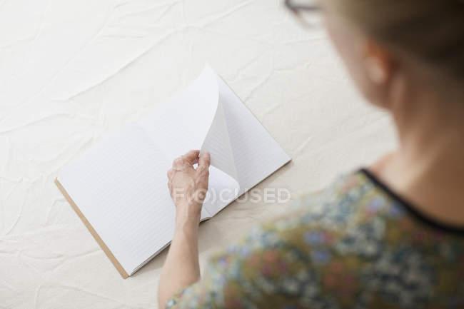 Через плечо или женщина, переворачивающая страницу пустой книги за столом — стоковое фото