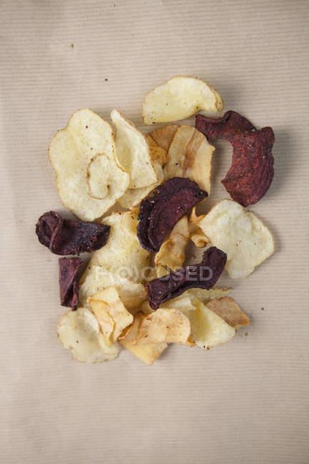 Copeaux de tir juste au-dessus des pommes de terre et de betterave rouge sur table — Photo de stock