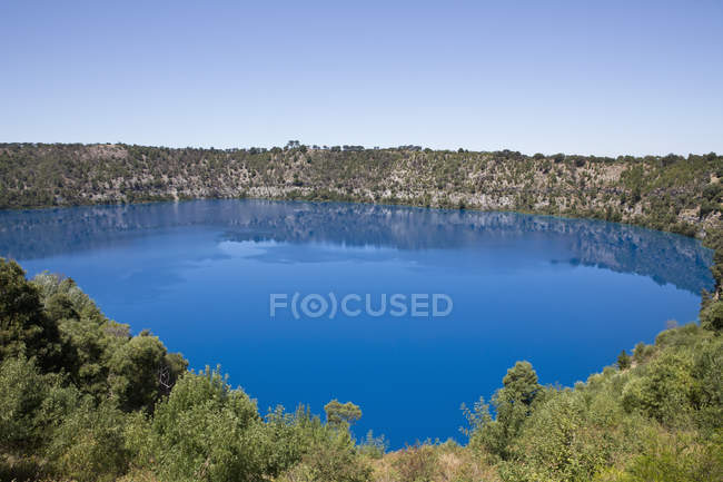 Tranquil view of pond surrounded by slopes against clear sky — Stock Photo