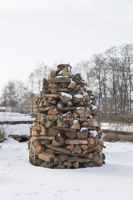 Firewood stacked in tower at snow-covered countryside scene — Stock Photo