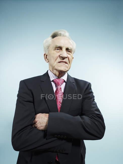 Елегантний старший чоловік з руками перетнув дивлячись незадоволення на синьому фоні — стокове фото