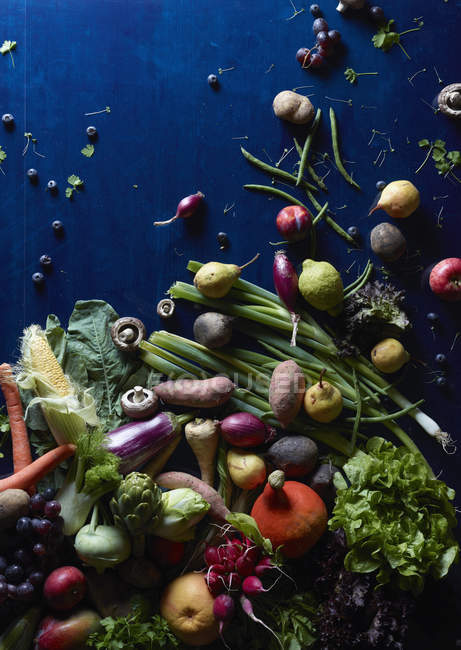 High angle view of fresh vegetables and fruits scattered on blue table — Stock Photo