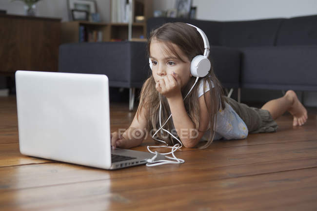 Girl using laptop while listening to music on hardwood floor — Stock Photo