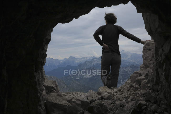 Rear view of woman standing on rock against mountains seen through cave — Stock Photo