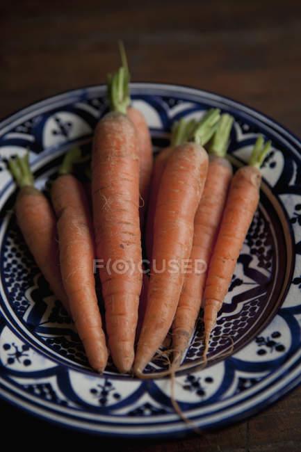 Montón de zanahorias en plato de cerámica - foto de stock