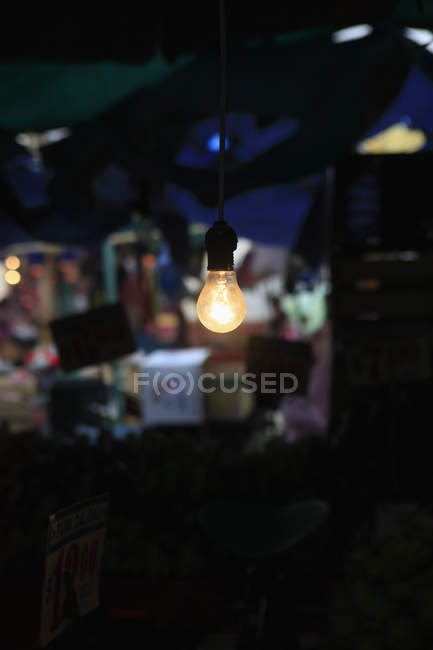 Close up view of lit light bulb in room — Stock Photo