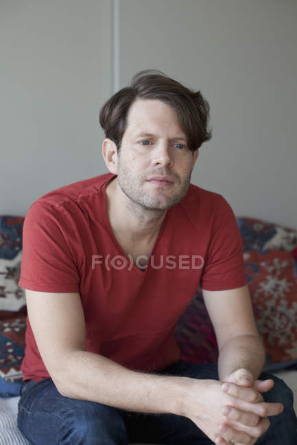 Thoughtful man sitting on sofa at home — Stock Photo