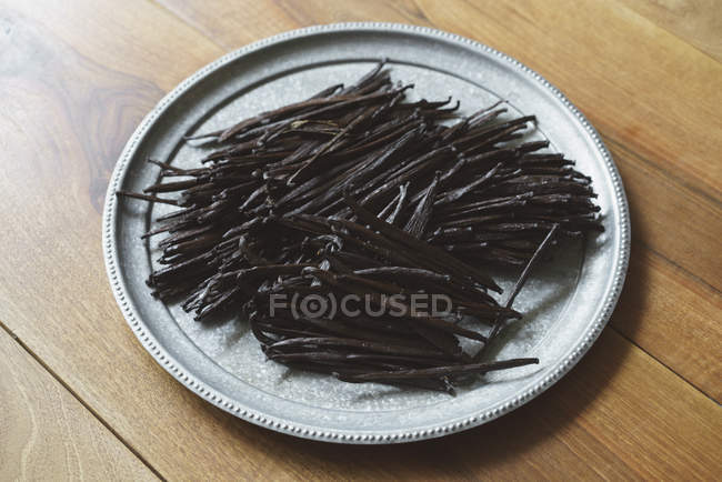 Low angle view of vanilla pods in metal round dish on table — Stock Photo