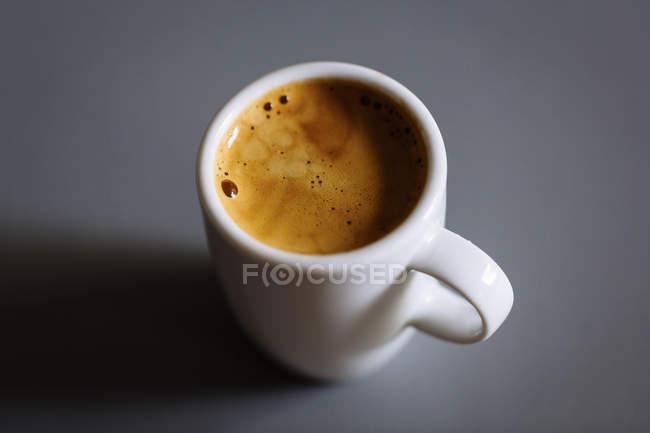 Vista de cerca del café en taza sobre fondo gris - foto de stock